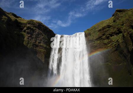 Ciel clair avec de l'eau verser l'une verdure luxuriante montagne en Islande. Arc-en-ciel et la cascade. Banque D'Images