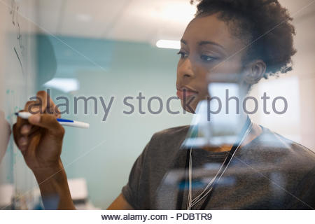 L'accent businesswoman writing on whiteboard in office Banque D'Images
