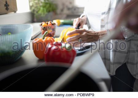 Close up senior woman couper les poivrons, la cuisson dans la cuisine Banque D'Images