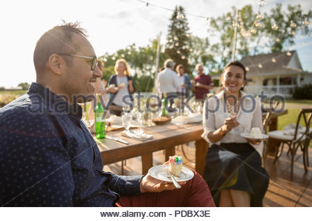 Smiling couple eating cake, célébrant de sunny garden party rural Banque D'Images