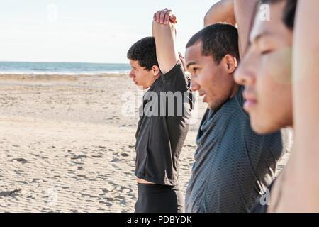 Coureurs Homme bras étirement sur sunny beach Banque D'Images