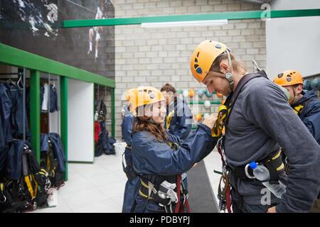Femme Homme aidant avec équipement zip line Banque D'Images