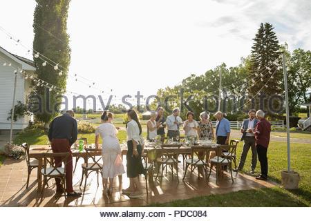 Fête d'amis, manger du gâteau à table de patio ensoleillé Banque D'Images
