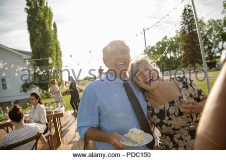 Couple heureux anniversaire célébrer, manger un gâteau at garden party Banque D'Images