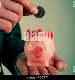 La main de l'homme à l'aide d'une pièce va mettre un hryvnia et une tirelire. Le programme financier. Banque D'Images