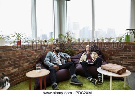 D'affaires créatifs sieste sur des poufs dans office Banque D'Images