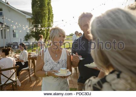 Fête d'amis, manger un gâteau at garden party Banque D'Images
