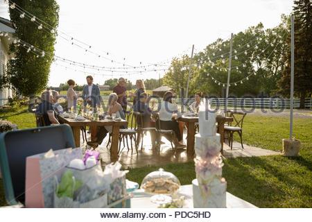 Friends celebrating derrière tiered gâteau de mariage, des cadeaux et des fleurs sur table patio Banque D'Images
