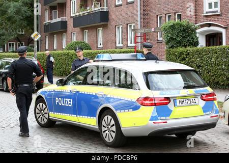 Hambourg, Allemagne. Le 08 août, 2018. Les agents de police sont debout devant un immeuble de Hamburg-Hamm où une jeune femme a été tuée. Apparemment, le père a tué sa fille, a déclaré un porte-parole de la police. Le suspect s'est enfui et a annoncé son suicide. Dans la recherche de l'homme suspect, un corps a été retrouvé à un poteau électrique dans Namur cet après-midi. Enquêtes sur son identité et l'historique de l'infraction poursuivie. Credit: Bodo Marks/dpa/Alamy Live News Banque D'Images