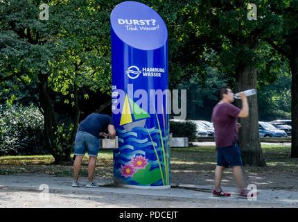 Hambourg, Allemagne. Le 08 août, 2018. Un homme assouvit sa soif à une colonne d'eau potable à l'extérieur de l'Alster. Axel Heimken Crédit:/dpa/Alamy Live News Banque D'Images