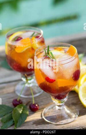 Vin rafraîchissant maison sangria ou punch aux fruits dans les verres. Sangria cocktails de fruits frais, de baies et de romarin. Sur une table rustique en bois,