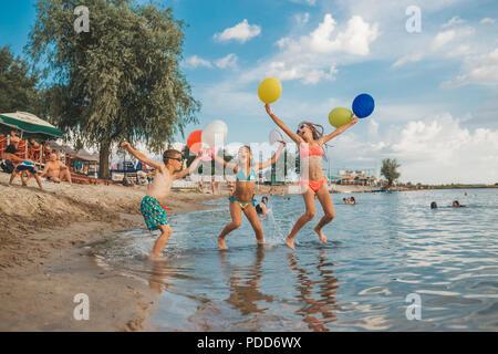 Heureux les enfants qui jouent avec des ballons dans la mer. Les enfants s'amuser en plein air. Vacances d'été et d'un style de vie sain concept Banque D'Images