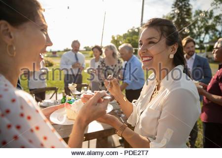 Smiling women eating cake, célébrant de sunny garden party rural Banque D'Images