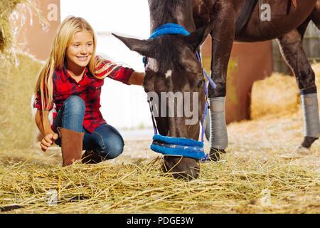 Transmission d'girl tout sourire tout en visitant l'dans stable Banque D'Images