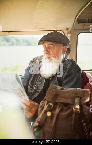 Un homme assis dans son vintage van regarde une carte routière Banque D'Images