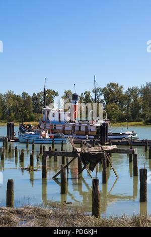 Héron perché sur les restes d'une ancienne conserverie de saumon avec des bateaux amarrés à l'arrière-plan Banque D'Images
