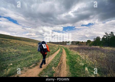 Randonneur dans avec de grandes balades à dos à la route de campagne près de la forêt contre le ciel nuageux dans Karkaraly parc national dans centre du Kazakhstan Banque D'Images