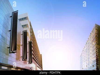 Verticale noire vierge bannières sur la façade de l'immeuble, la conception de maquettes. Store maquette drapeaux dans la rue. Modèle de mât extérieur sur le côté de la boutique de l'extérieur. Trois lettrages pendaison le mur. Banque D'Images