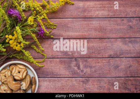 Agréable composition de fleurs d'automne et les cookies sur un fond sombre. concept d'automne. Télévision, vue de dessus mise en page Banque D'Images