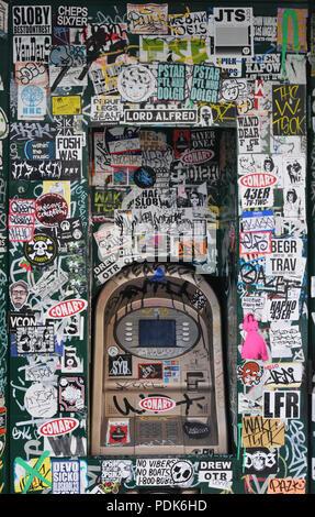 Autocollants et graffiti couvrent un guichet automatique dans le quartier des Arts à Los Angeles, Californie. Banque D'Images