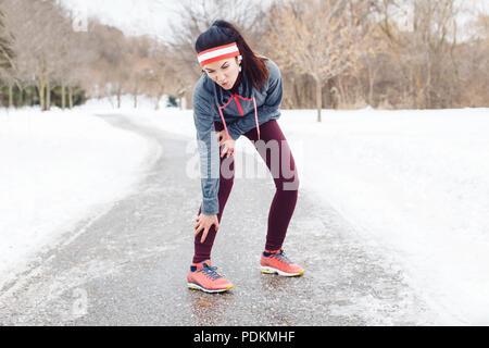 Portrait de jeune femme caucasienne la sensation de douleur dans les jambes après le jogging à l'extérieur du parc en hiver. Jeune fille ayant une blessure lors de l'exécution en plein air excercising Banque D'Images