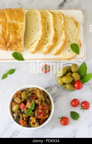 Caponata ou ratatouille à partir d'une variété de légumes servi avec pain ciabatta et olive. Focus sélectif. Banque D'Images