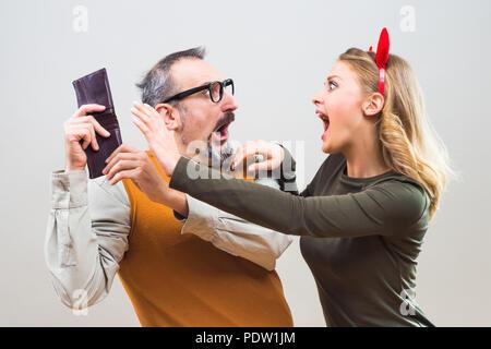 Nerdy man essaie de cacher l'argent de sa femme parce qu'elle tiens à tout dépenser. Banque D'Images