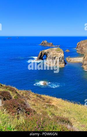 Enys Dodnan arch, chevalier armé pile mer et phare de la drakkars lointain South West Coast Path, Sennen, Lands End, Cornwall, England, UK. Banque D'Images