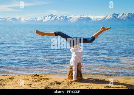 Jeune fille faire part position sur plage avec Sierra montagnes en arrière-plan, le lac Tahoe, Pacé, Nevada, USA Banque D'Images