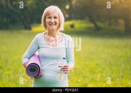 Portrait of senior woman holding sportive bouteille d'eau et mat dans la nature.Image est volontairement tonique. Banque D'Images