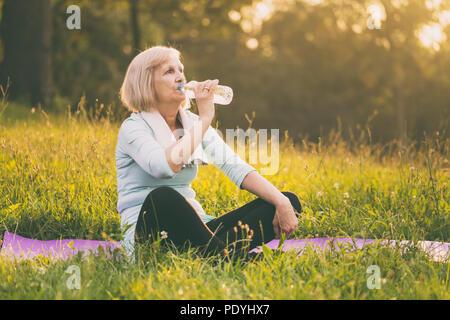 Active senior woman l'eau potable au cours de l'effort.Image est volontairement tonique. Banque D'Images