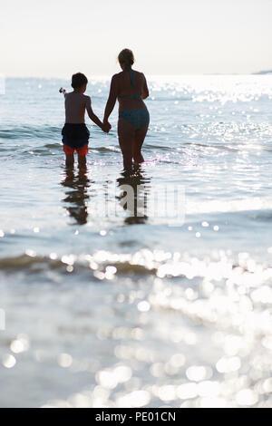 Mère et fils s'amusant de sauter les vagues de la mer en début de soirée alors que le soleil se couche et est sur le scintillement de l'eau d'un bleu pur Banque D'Images