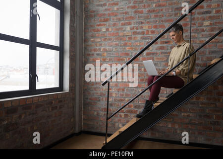 Businesswoman using laptop on stairs Banque D'Images