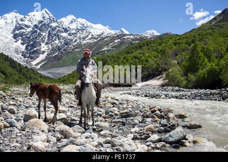 L'homme sur un cheval traversant une rivière dans les montagnes du Caucase en Géorgie, Svaneti