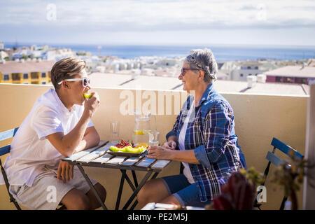 Professionnels activité de loisirs sur la terrasse le petit déjeuner sur le toit avec des sourires et de bonheur pour grand-mère et ado famille peuples caucasiens un océan. Banque D'Images