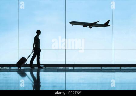 Silhouette de femme à l'aéroport voyager avec des bagages valise, voyages et tourisme, les billets d'avion concept Banque D'Images