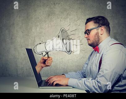 Businessman sitting at table fonctionne sur ordinateur crier avec un mégaphone poussant à partir d'un écran d'ordinateur portable Banque D'Images