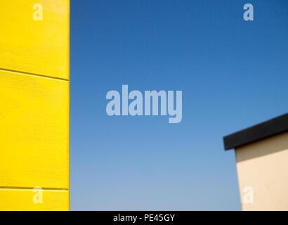 De couleur les bords de deux cabines de plage, une jaune et une couleur crème, contre un ciel bleu clair Banque D'Images
