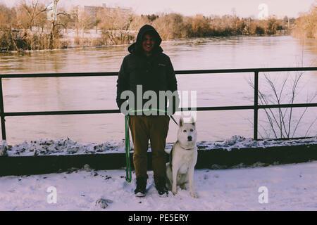 Jeune homme à côté d'une rivière en hiver avec son husky de Sibérie. Banque D'Images