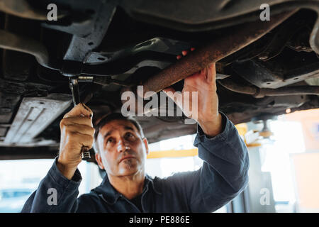 L'homme de serrer un tuyau de silencieux avec clés à cliquet en auto garage. Mécanicien travaillant dans le cadre d'un levé à l'atelier de réparation. Banque D'Images