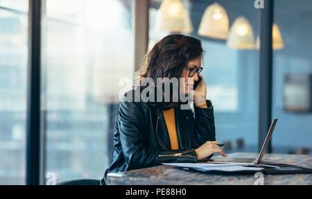 Business Woman sitting travaillant au bureau et talking on mobile phone. Femme d'affaires occupé à travailler à son bureau. Banque D'Images