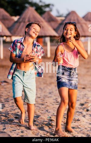 Heureux les enfants s'amuser tout en marchant le long d'une plage de sable. L'été et travel concept Banque D'Images
