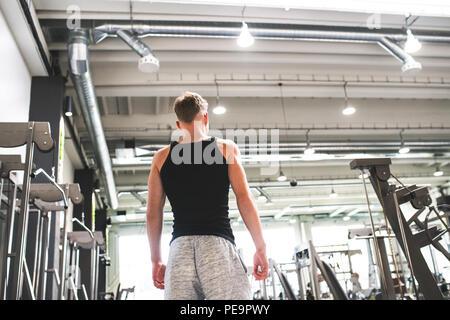 Jeune homme dans une salle de sport moderne, crossfit. Vue arrière. Copier l'espace. Banque D'Images