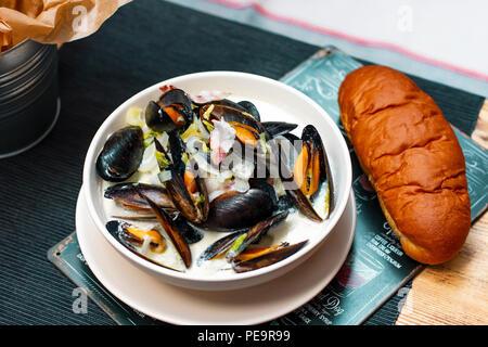 Moules aux oignons et lardons à la crème dans une assiette avec du pain sur la table