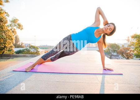 Femme de remise en forme de planches de faire les exercices de yoga en plein air sur la plage pier Banque D'Images