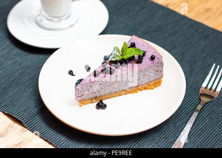 Blueberry Cheesecake aux fruits rouges et menthe et latte café sur la table Banque D'Images