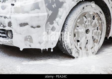 Lave-linge noir avec mousse active. Concept de lavage de voiture.Voiture en mousse. Banque D'Images