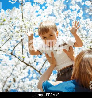 Mère tenant son fils tout-petit garçon élevé dans ses bras, la floraison des fleurs d'arbres blancs et ciel bleu sur l'arrière-plan, tout-petit rire sourire montrant sa