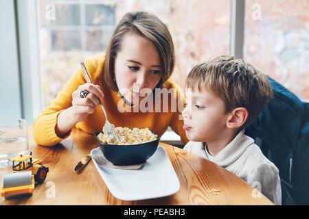 Portrait of white Caucasian famille heureuse, mère et fils, assis dans le café à table, de manger des spaghettis, pâtes alimentaires de vie authentique Banque D'Images