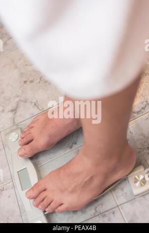 Pieds de l'homme debout sur l'échelle de poids Banque D'Images